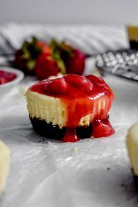 Mini White Chocolate Cheesecakes with strawberry sauce