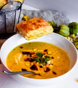 Roasted Corn & Tomatillo Chowder  in a bowl with a biscuit