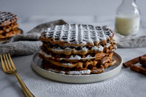 Gingerbread Waffles stacked on a plate with powdered sugar