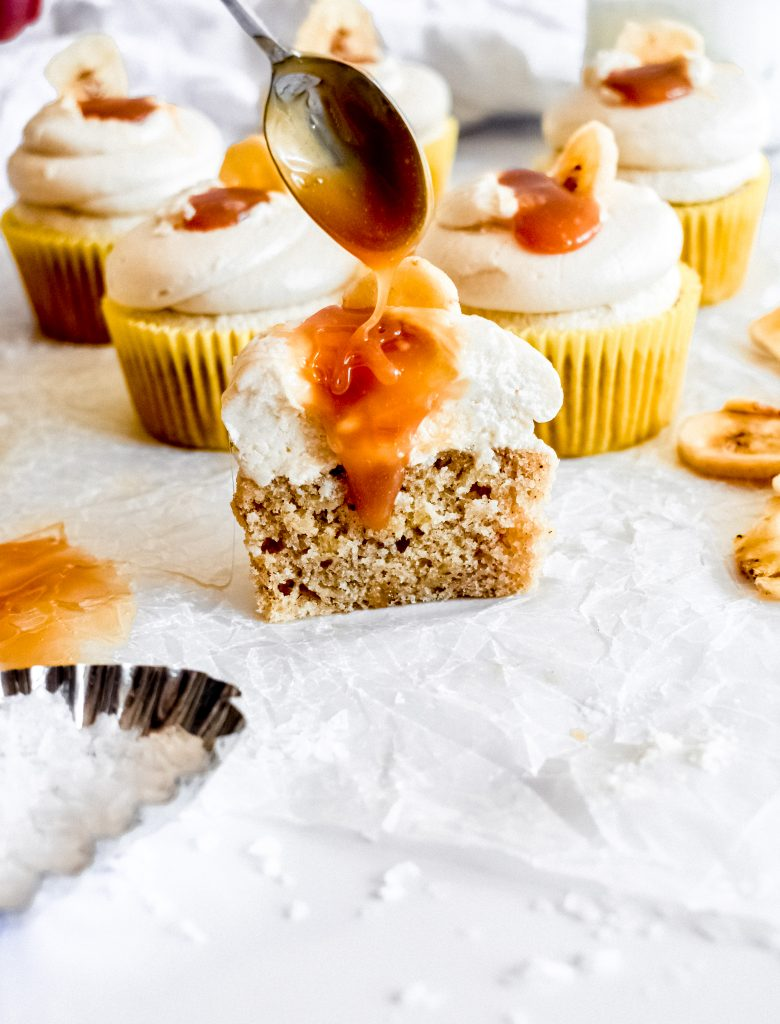 roasted banana cupcakes with salted caramel frosting on parchment with caramel drizzle