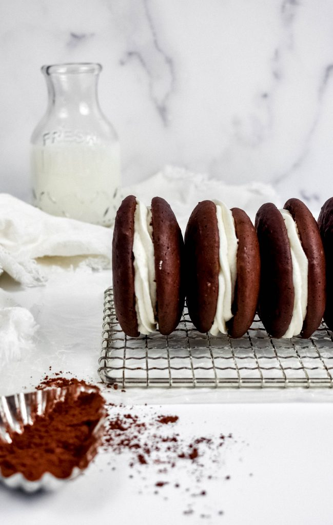 Chocolate Guinness Whoopie pies side by side with cocoa powder