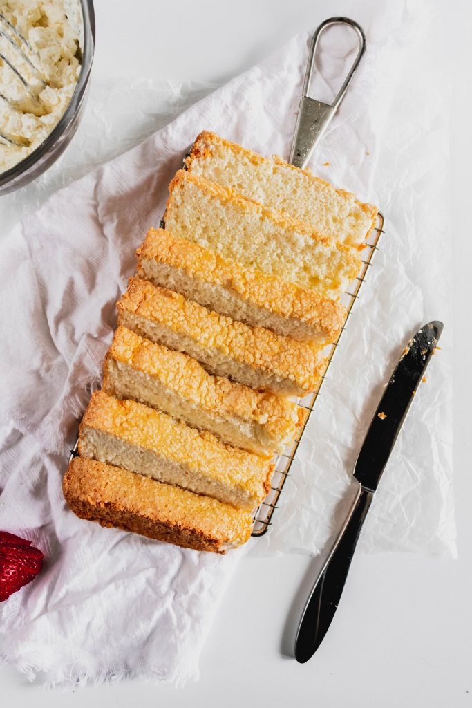 Easy Angel Food Cake -- in a loaf pan on a rack with a knife