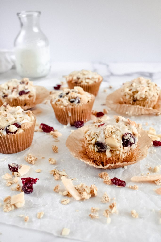 Easy Banana Muffins with Granola Crumble with wrappers open on parchment paper with granola scattered around