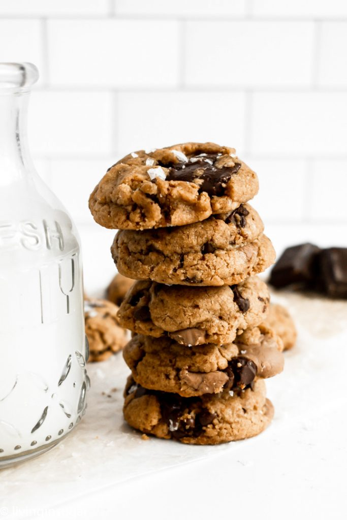 peanut butter chocolate chunk cookies stacked next to milk jug
