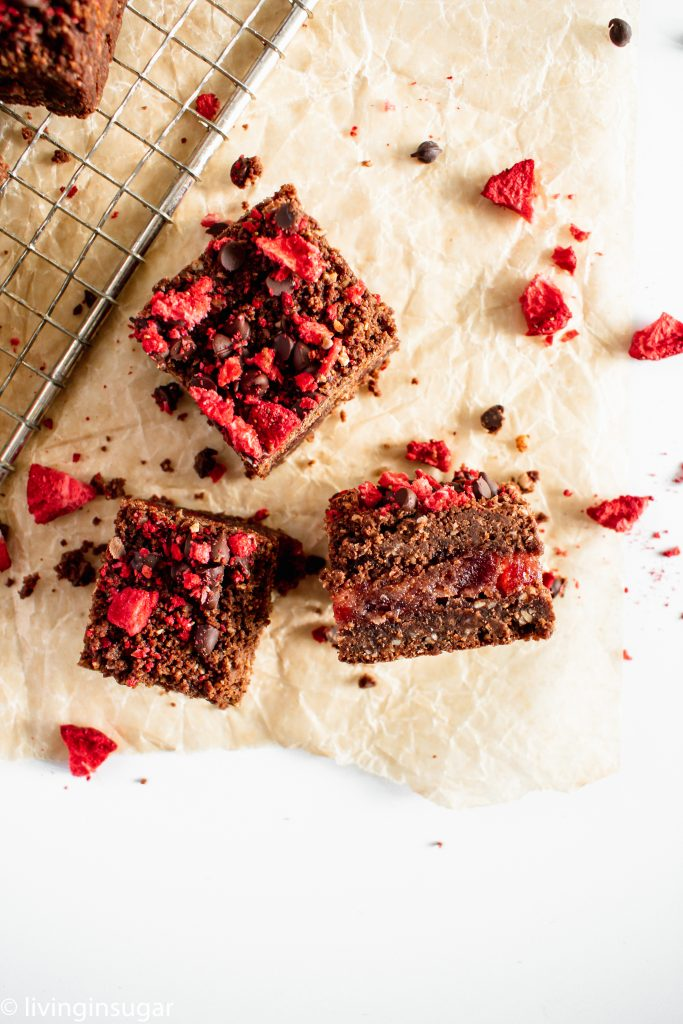 Chocolate Strawberry Crumble Bars three pieces, with filling showing